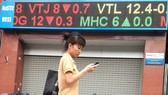 A woman walks past an electronic board showing share prices at Bao Viet Securities Co on Ba Trieu street in Hanoi (Photo: VNA)