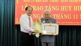 Đồng chí Tất Thành Cang trao Huy hiệu 65 năm tuổi Đảng cho đồng chí Phạm Văn Bảy