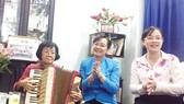 Đồng chí Nguyễn Thị Quyết Tâm (giữa) cùng gia đình liệt sĩ Nguyễn Ngọc Tấn đàn, hát những ca khúc nổi tiếng trong phong trào học sinh, sinh viên Sài Gòn - Gia Định