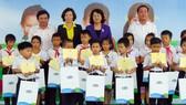 國家副主席鄧氏玉盛(後排右二)向維貞鄉清貧優秀生贈送奶品和助學金。(圖源:玉詩)