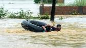 圖為8月13日,尼泊爾比爾根傑帕薩區民眾在洪水中。(圖源:AFP)