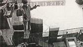 根據該銀行監控提取的圖片,歹徒蒙面戴著安全帽,左手持著狀似手槍,右手拿著手提袋扔進交易櫃台,強迫人員把錢放進手提袋。(圖源:明英)