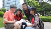 """大學生在""""九‧二三""""公園以英語與外國人溝通。"""