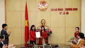 勞動與榮軍社會部副部長陶紅蘭(中左)向阮翠姮同志頒授《家庭與少兒雜誌》副總編輯職務的委任《決定》。