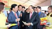 政府總理阮春福參觀農業展位。(圖源:光孝)