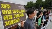 眾人集中在漢城的韓國總統辦事處外面高舉要求懲處某漁船船長涉嫌毒打兩名越南漁民事件的標語牌。(圖源:韓國時報)