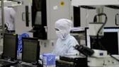 一名工人在新加坡某一微芯片製造廠監控生產過程。(圖源:路透社)
