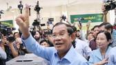"""洪森在柬干拉省大金歐市大金歐分區投票點伸出已""""投票印記""""的右手食指。(圖源:互聯網)"""