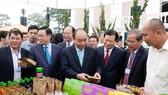 政府總理阮春福參觀農業加工產品展位。(圖源:光孝)