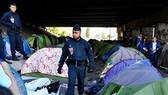 法國警察在移民撤離營地後進行檢查留下的帳篷。(圖源:PressTV)
