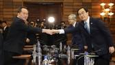 韓統一部長官趙明均(右)與朝祖國和平統一委員會委員長李善權握手合影。(圖源:新華網)