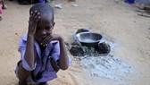 在索馬里首都摩加迪沙郊外的難民營,一個孩子蹲坐在地。(圖源:Getty Images)