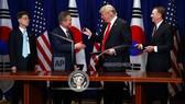 韓總統文在寅(左)和美總統特朗普交換韓美FTA修訂案文件。(圖源:AP)