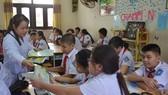 衛生防疫宣傳隊員向學生發放非傳染病預防要點傳單。(示意圖源:阮華)