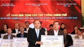 Thủ tướng Nguyễn Xuân Phúc trao quà tặng cho 20 huyện nghèo qua đấu giá trái bóng và áo Đội tuyển U23 Việt Nam. Ảnh: TTXVN
