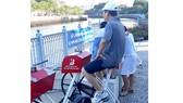 Tay cầm xe đạp lọc nước bị tháo mất, người dân muốn tập phải chống nạnh đạp xe. Kế bên là chiếc xe đạp lọc nước với yên xe đã gãy gục