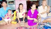 Vợ chồng chị Lợi (bên trái) và 2 hội viên khiếm thị đang học nghề đan thảm chùi chân tại nhà