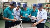 Anh Trịnh Minh Đức (bìa phải) cùng các đồng nghiệp thảo luận và thiết kế, chế tạo thành công máy kiểm tra dây điện