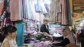 Khách hàng tìm mua khăn quàng cổ tại một sạp ở chợ Bến Thành ngày 26-10