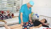 Bác sĩ Nguyễn Văn Tiến, Trưởng khoa Ngoại 1, Bệnh viện Ung bướu TPHCM, đang thăm khám cho bệnh nhân ung thư