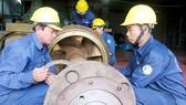 Anh Võ Dũng (bìa phải) cùng đồng nghiệp khắc phục sự cố máy móc
