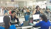 Người dân lấy số thứ tự chờ mua vé tàu Tết tại ga Sài Gòn