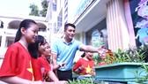 Thầy Lưu Hoàng Phúc hướng dẫn HS cách trồng và chăm sóc rau củ quả tại vườn ươm của trường