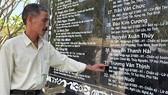 Ông Trương Văn Cẩn bên tấm bia liệt sĩ  khắc tên em trai mình