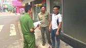 Ông Nguyễn Văn Ba (giữa) cùng Công an phường Xuân An tuyên truyền phòng chống tội phạm cho một cơ sở kinh doanh trên địa bàn