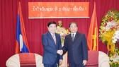 Chủ tịch UBND TPHCM Nguyễn Thành Phong chúc mừng Tổng Lãnh sự Lào tại TPHCM Somxay Sanamoune nhân dịp kỷ niệm 42 năm Quốc khánh nước Cộng hòa Dân chủ Nhân dân Lào. Ảnh: hcmcpv