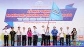 Chủ tịch UBND TPHCM Nguyễn Thành Phong trao cờ phát động ra quân thực hiện năm An toàn giao  thông 2018. Ảnh: QUỐC HÙNG