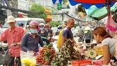 Khách hàng chọn mua bánh ú, trái cây sát chợ Hòa Hưng, quận 10, TPHCM, sáng 18-6. Ảnh: THI HỒNG