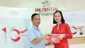 Một khách hàng có khoản vay tín chấp mới vui vẻ đón nhận quà tặng đặc biệt từ Công ty Tài chính Prudential Việt Nam nhân sự kiện kỷ niệm 10 năm thành lập
