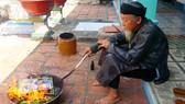 Một người dân ở xã đảo Long Sơn (Vũng Tàu) đốt vàng mã cho người cháu đã mất. Ảnh: VŨ ANH