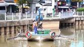 Công nhân vớt rác dưới kênh