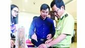 Một số khách mời, người tiêu dùng phân biệt sản phẩm thật với  hàng giả mạo tại một hội thảo ở TPHCM