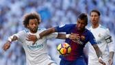 Marcelo (trái, Real Madrid) tranh bóng với Paulinho (Barcelona)
