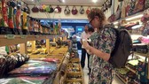 Khách nước ngoài lựa chọn sản phẩm tại cửa hàng bán lưu niệm. (Ảnh: Gia Thuận/TTXVN)
