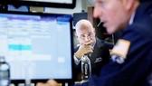 Nhân viên giao dịch theo dõi chỉ số chứng khoán tại Sàn giao dịch chứng khoán New York (Mỹ)