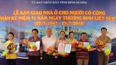 Ông Đặng Minh Hưng (thứ 3 từ trái qua) tặng hoa cho các cá nhân được nhận nhà