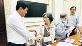 Phó Chủ tịch UBND TPHCM Huỳnh Cách Mạng (trái) đang trao đổi với người nhà của ông Nguyễn Anh Hoàng. Ảnh: KIỀU PHONG