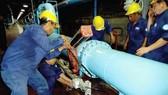 Công nhân thi công đường ống nước. Ảnh: VÂN HÀ