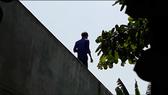 Nam thanh niên nghi ngáo đá cố thủ trên mái nhà dân. Ảnh cắt clip