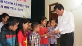 Thay mặt Báo SGGP, Phó Tổng Biên tập báo SGGP Nguyễn Ngọc Anh trao quà cho các cháu học sinh nghèo học giỏi xã Phúc Thọ