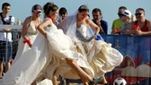 Tuy có phần vướng víu nhưng những chiếc váy cưới trắng chính là điểm nhấn khiến các cô gái thêm nổi bật tại khu vực Fan Fest. Ảnh: Reuters