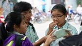 Thí sinh bàn luận sau khi kết thúc môn thi tiếng Anh tại hội đồng thi Nguyễn Thị Thập, quận 7. Ảnh: HOÀNG HÙNG