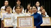 Phó Bí thư Thành ủy TPHCM Võ Thị Dung trao tặng bằng khen cho các em đạt thành tích cao trong học tập. Ảnh: HOÀNG HÙNG