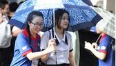 Các tình nguyện viên tại TPHCM hỗ trợ thí sinh vào phòng thi trong cơn mưa chiều 23-6 tại Hội đồng thi Trường THPT Marie Curie. Ảnh: HOÀNG HÙNG