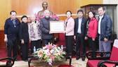 Đại diện gia đình cụ Hoàng Thị Minh Hồ trao tiền ủng hộ đồng bào miền Trung
