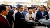 Phó Thủ tướng Vũ Đức Đam và lãnh đạo các bộ ngành tham quan, nghe giới thiệu về dự án thiết bị bay siêu nhẹ ứng dụng cho sản xuất nông nghiệp công nghệ cao. Ảnh: TRẦN BÌNH